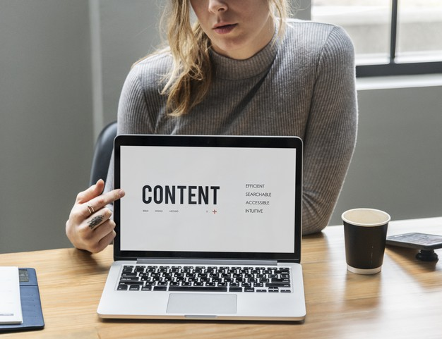Blond woman pointing at a laptop screen Free Photo