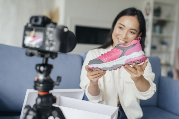 Smiley woman vlogging with her sports shoes Free Photo